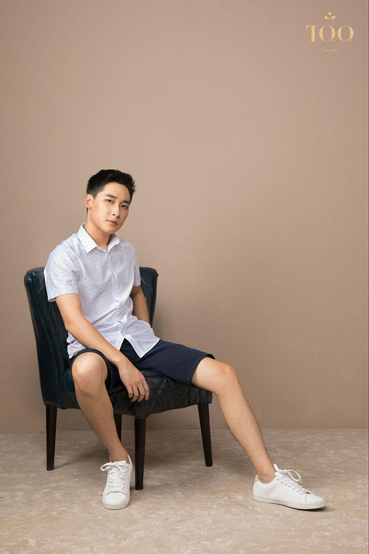 áo sơ mi trắng ngắn tay họa tiết nhỏ kết hợp cùng quần short tối màu và giày sneaker trắng