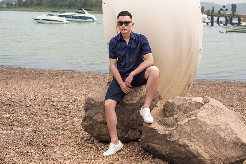Kết hợp áo sơ mi ngắn tay kẻ sọc với quần short và giày thể thao tạo nên phong cách trẻ trung, năng động