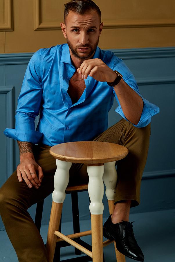 sơ mi dài tay có màu xanh hoàng đế nổi bật kết hợp cùng quần kaki nâu và giày da