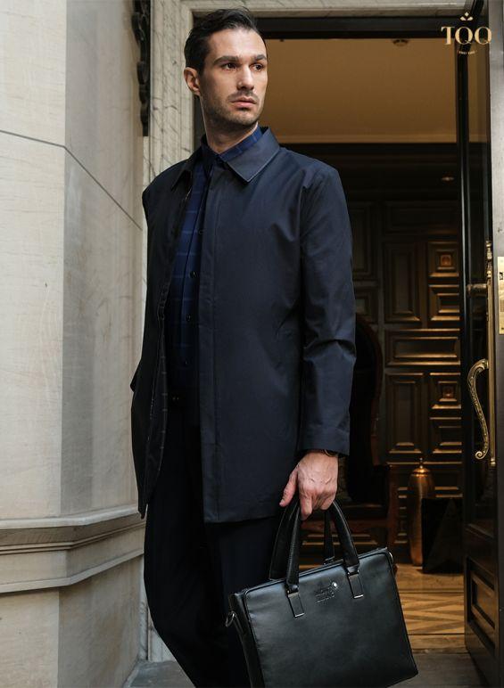 Một chiếc áo khoác dáng dài màu đen lịch lãm mặc với áo sơ mi kẻ xanh navy